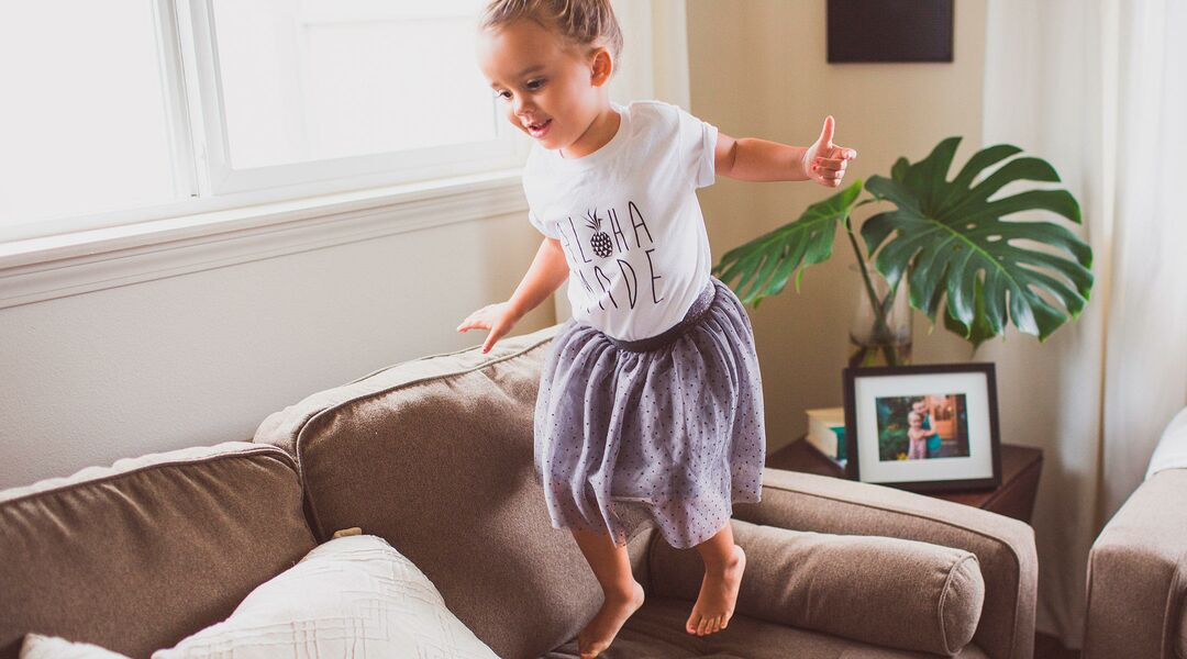 happy little girl jumping on the couch at home