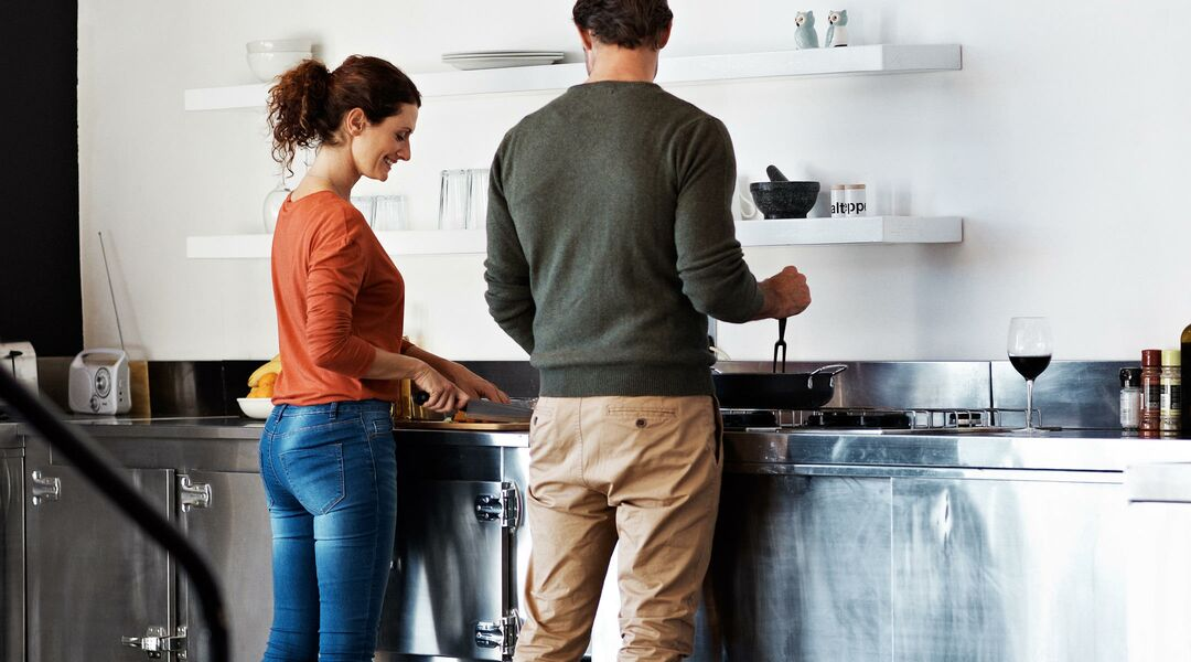 Adult couple preparing meal in industrial kitchen.