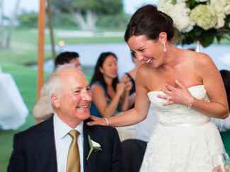A bride laughs with her father at her wedding reception