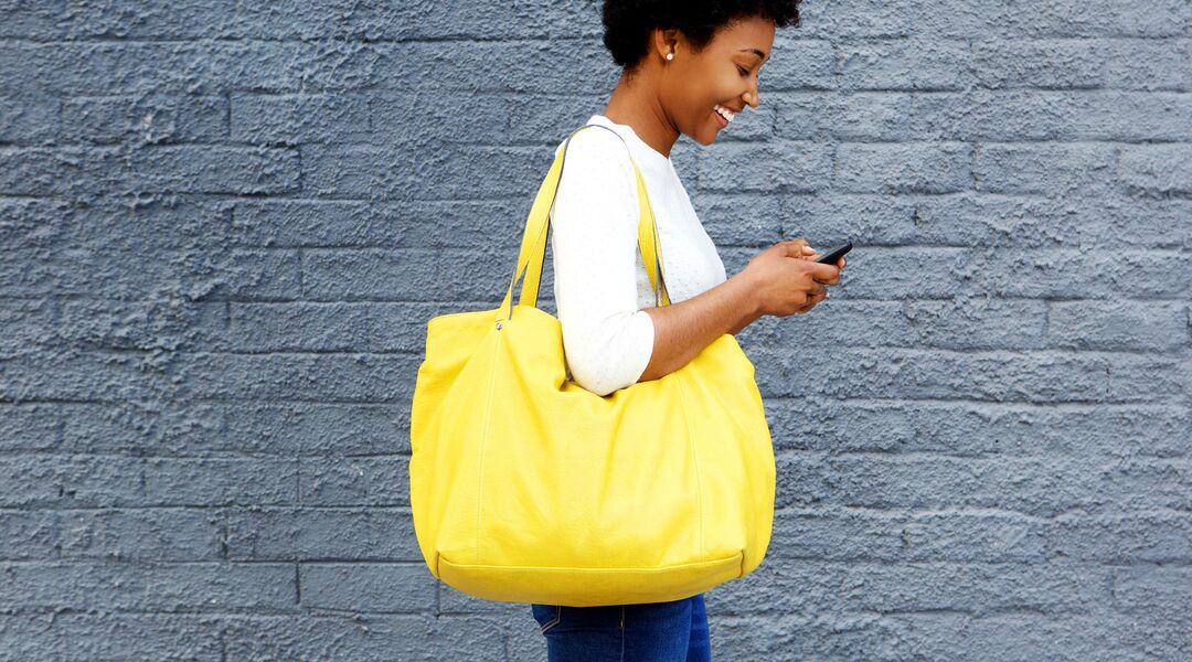 woman laughing holding yellow diaper bag
