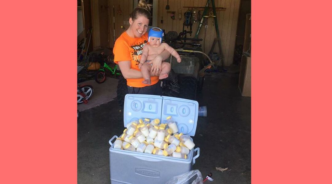 mom holding baby over cooler of milk donations