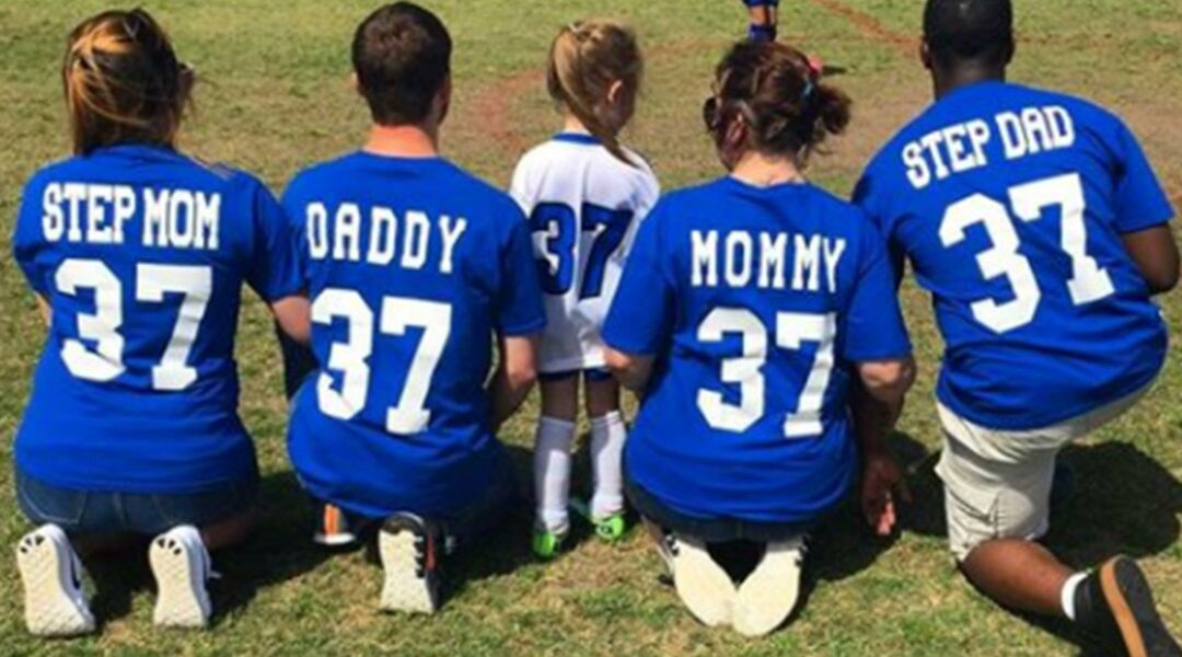 Mom, dad, step mom and step dad wearing jerseys at their daughter's soccer game.