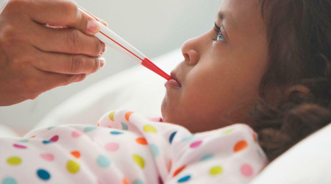 sick little girl getting temperature taken