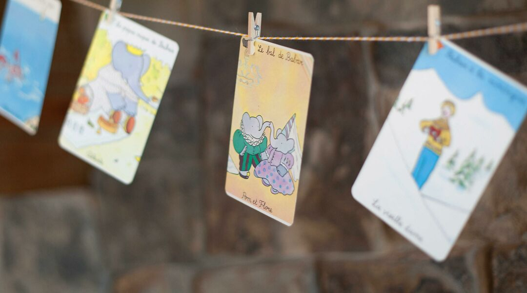 Babar themed birthday party, detail of babar story drawings hanging from fireplace.
