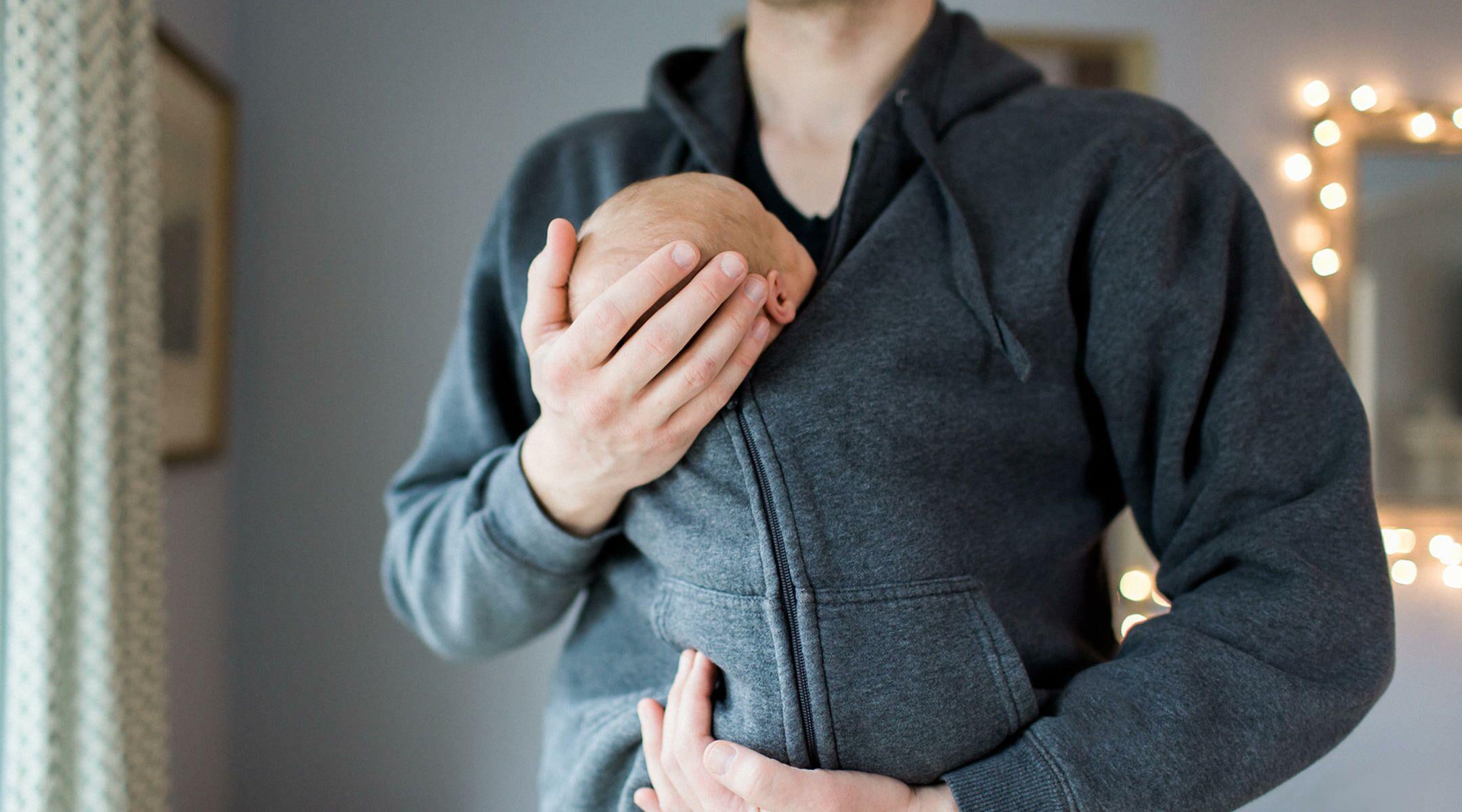 dad holding newborn inside his sweatshirt