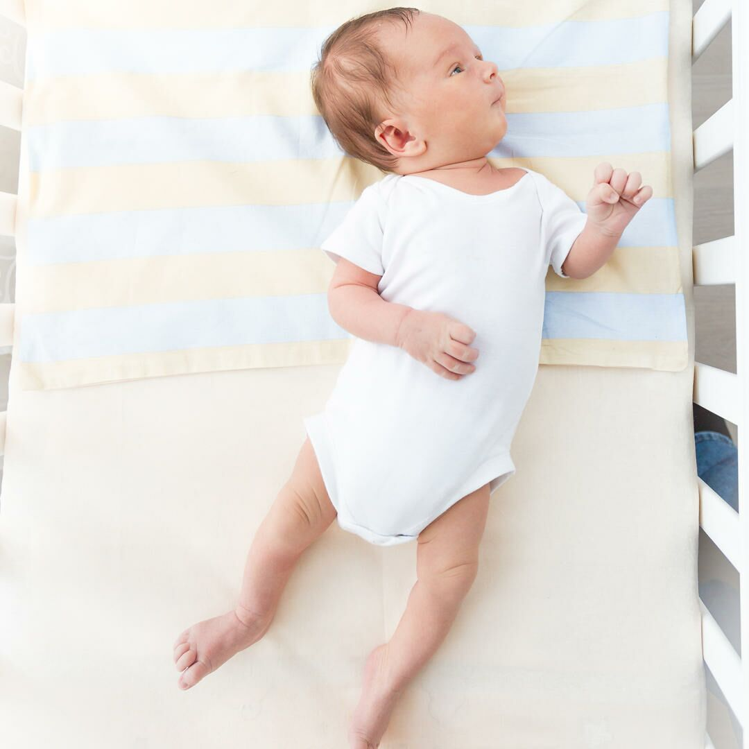 Baby laying on back in crib with yellow bedding
