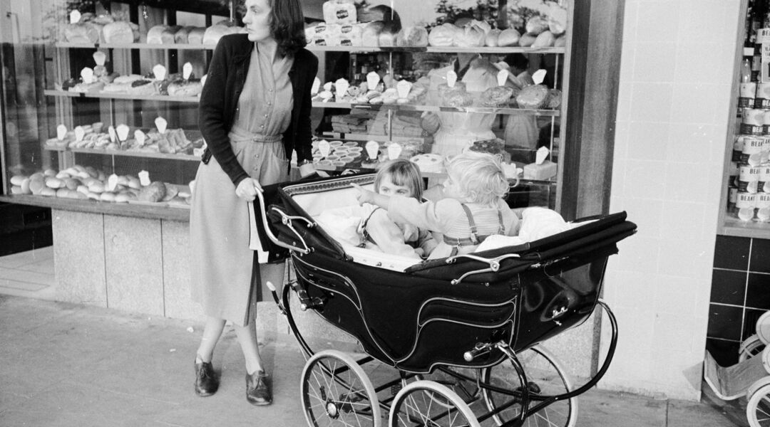 black and white photo of mom with pram and two children