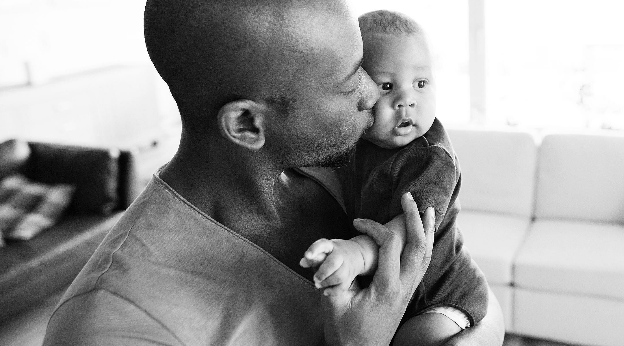 Young afro-american father at home holding his cute baby son in his arms, kissing him on cheek.