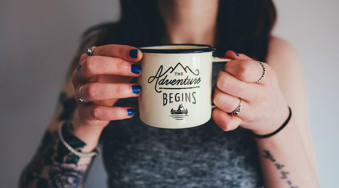 Close up of alternative woman with blue nail polish holding mug that says: the adventures begin.