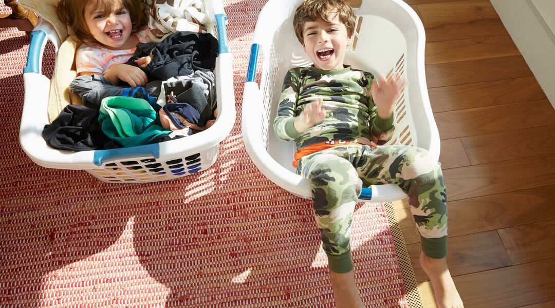 laughing kids having fun in laundry baskets at home