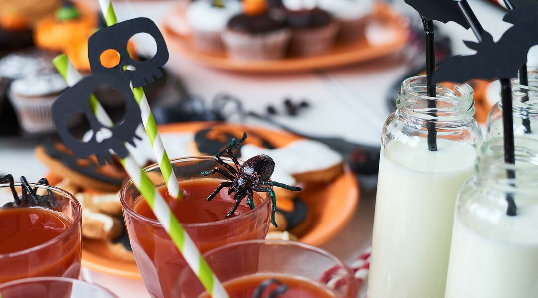 Close-up of toy spider on drinking glass with decorated straw