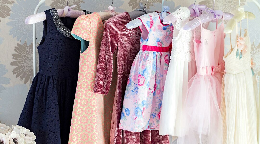 Designer baby clothes hanging on a rack