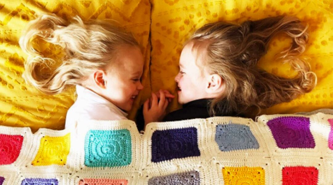 Twin girls facing each other under quilt