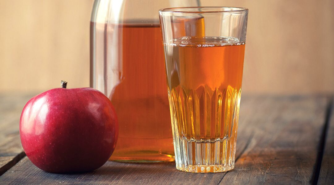 Glass of apple juice with jug on wooden surface.
