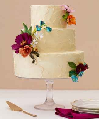 Round ivory buttercream cake with paper flowers