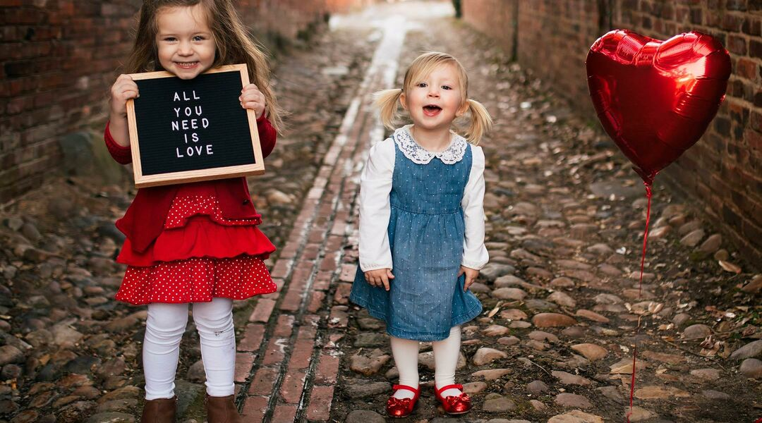 two little girls dressed for valentine's day and holding letterboard