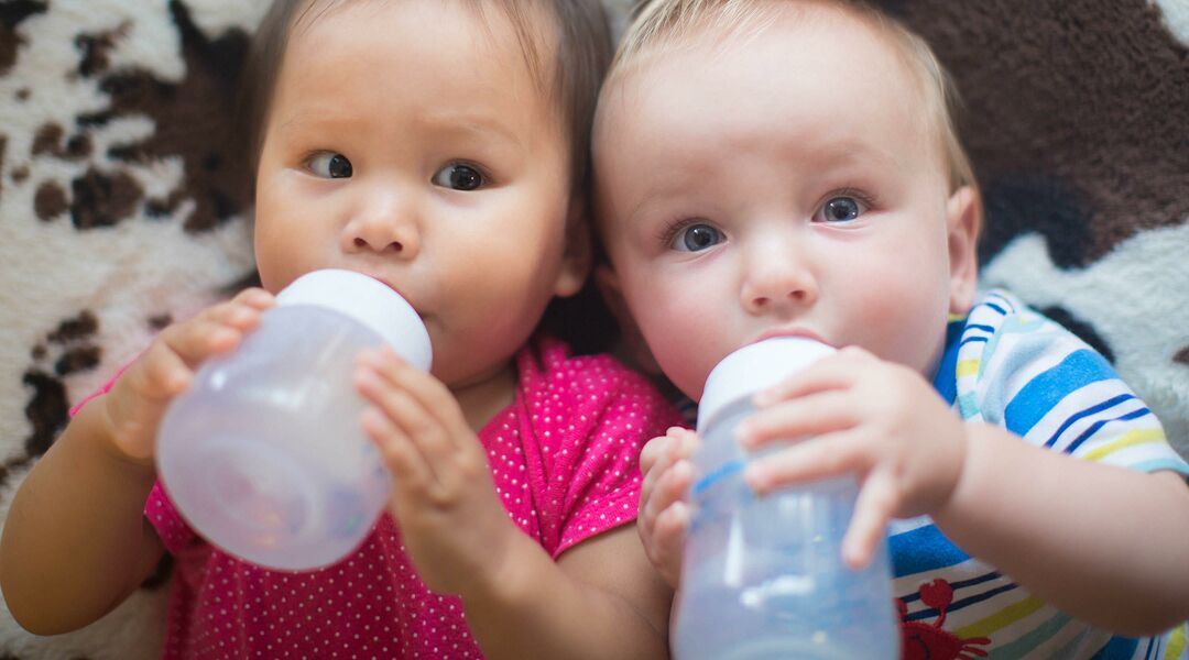 Two babies holding bottles and drinking