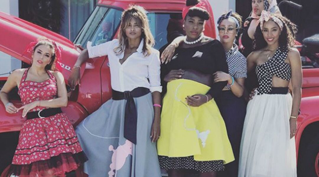 Serena Williams and celebrities posing in 1950s poodle skirts in front of a vintage red pickup truck at her baby shower