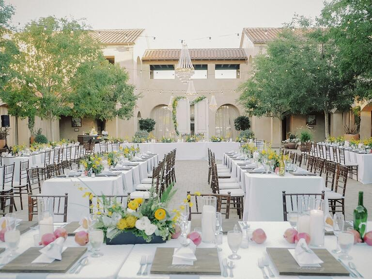 An outdoor reception with chandeliers and ranunculus