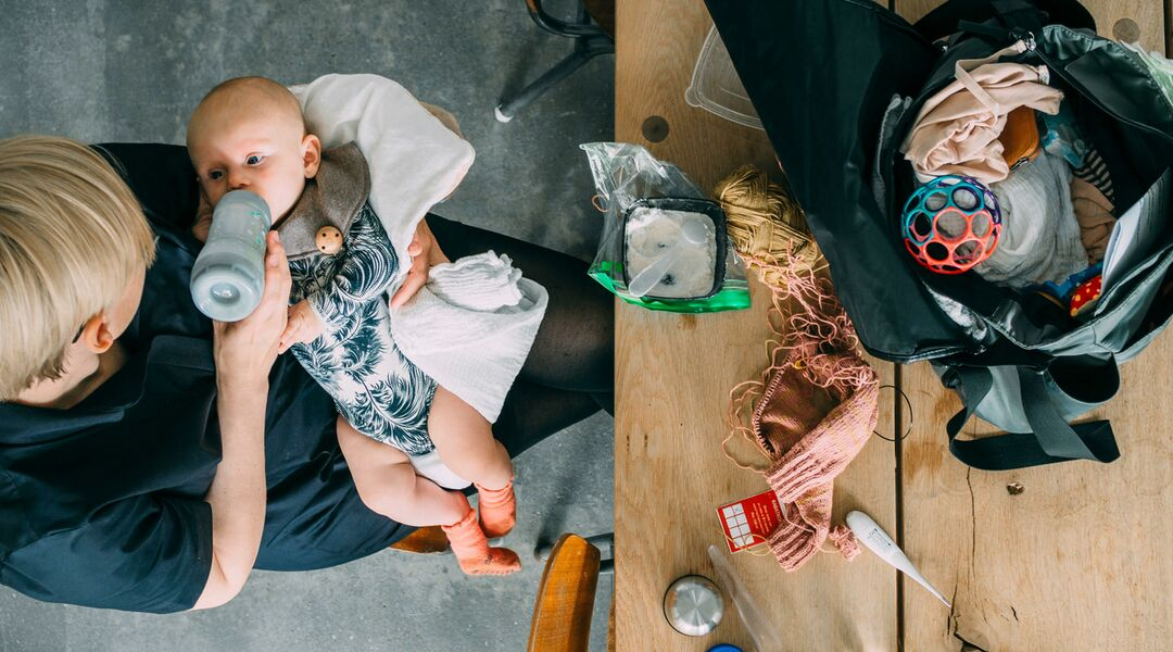 new mom feeding baby bottle with diaper bag contents strewn about