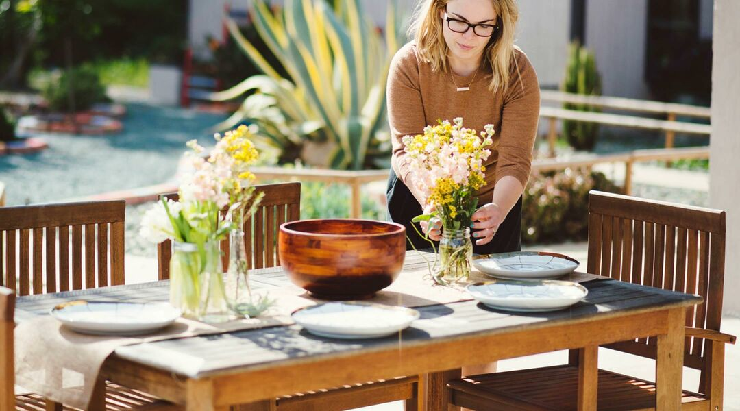Woman getting outdoor table ready for entertaining.