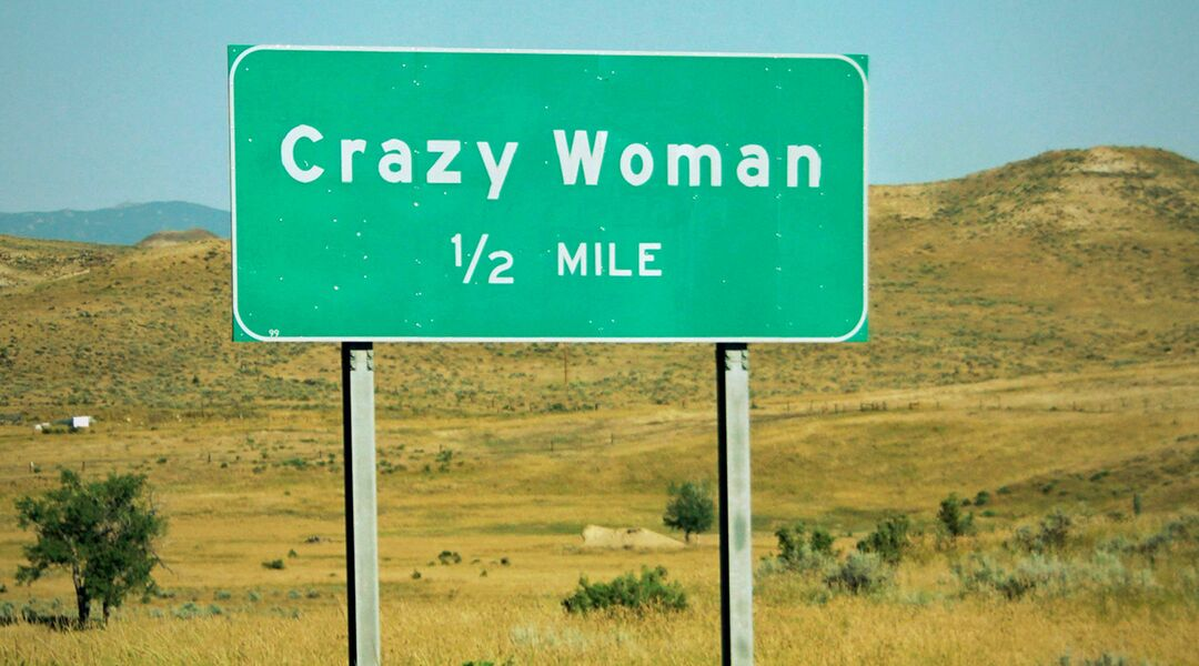 highway sign says crazy woman half mile