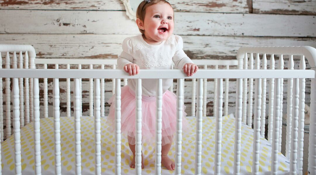 baby girl standing in her crib in her nursery