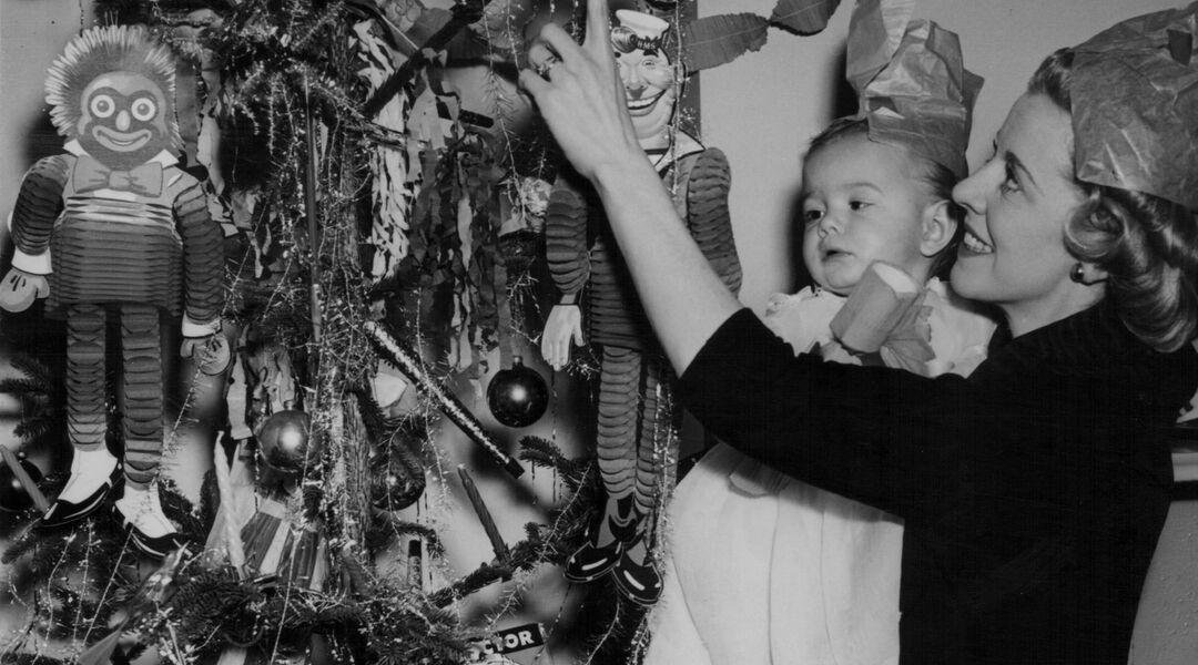 Retro photo of mom holding baby while decorating Christmas tree.