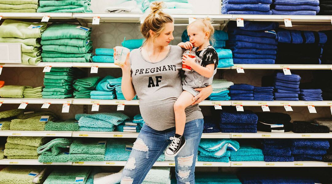 a shot of Page D. Miller holding her daughter Avery in a Target in front of a towel display