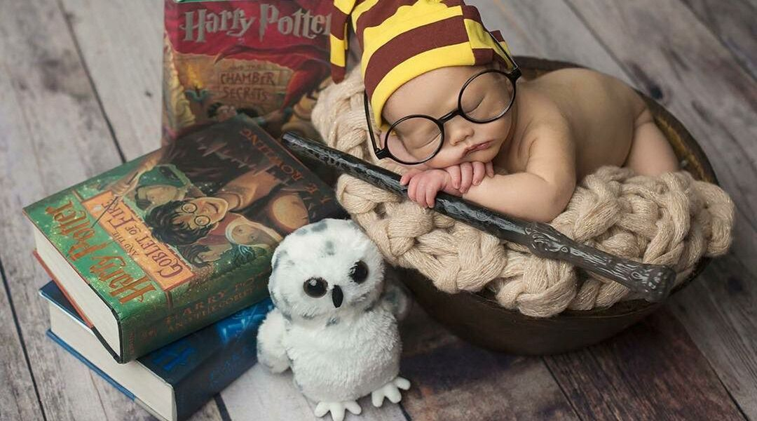 A baby sleeps with a Gryffindor sleeping cap and wand in hand, next to three Harry Potter books and a stuffed Hedwig owl.