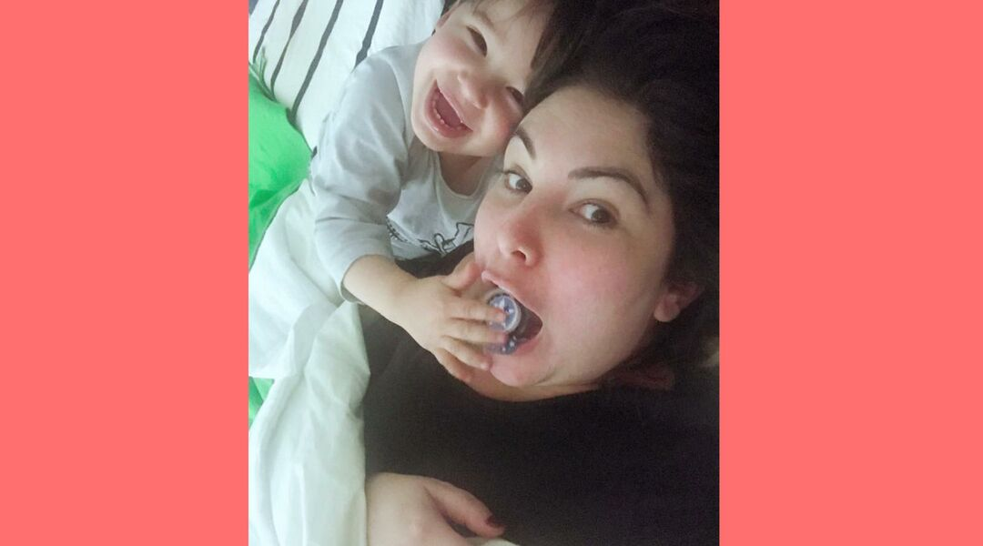 Son putting his pacifier in mom's mouth