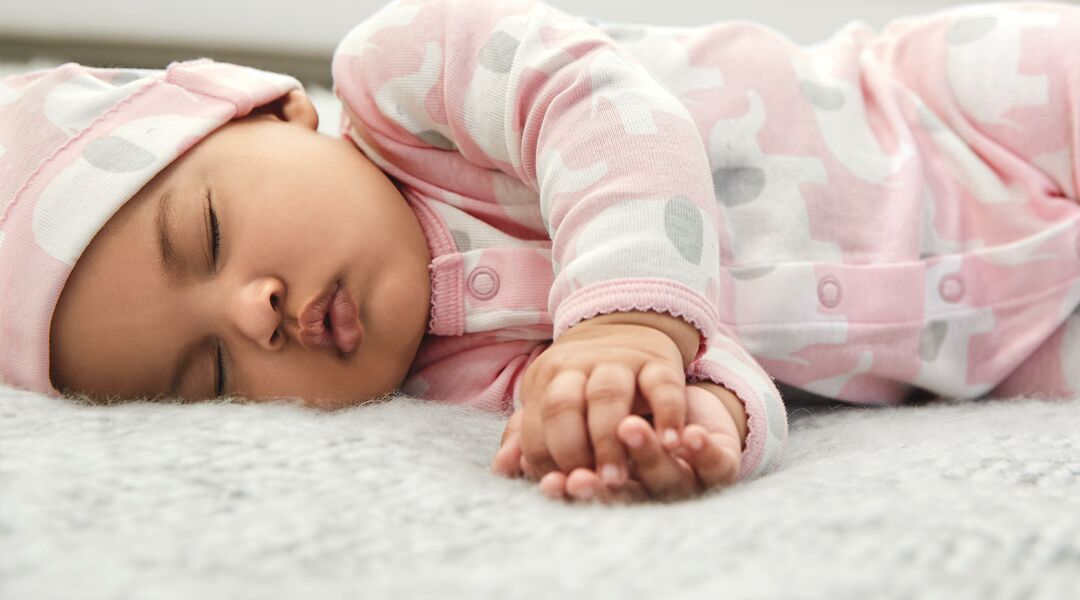 baby sleeping wearing pink elephant pajamas