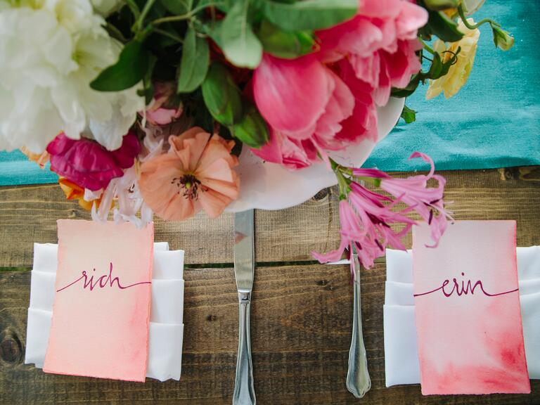 Two pink escort cards sit next to each other at a place setting