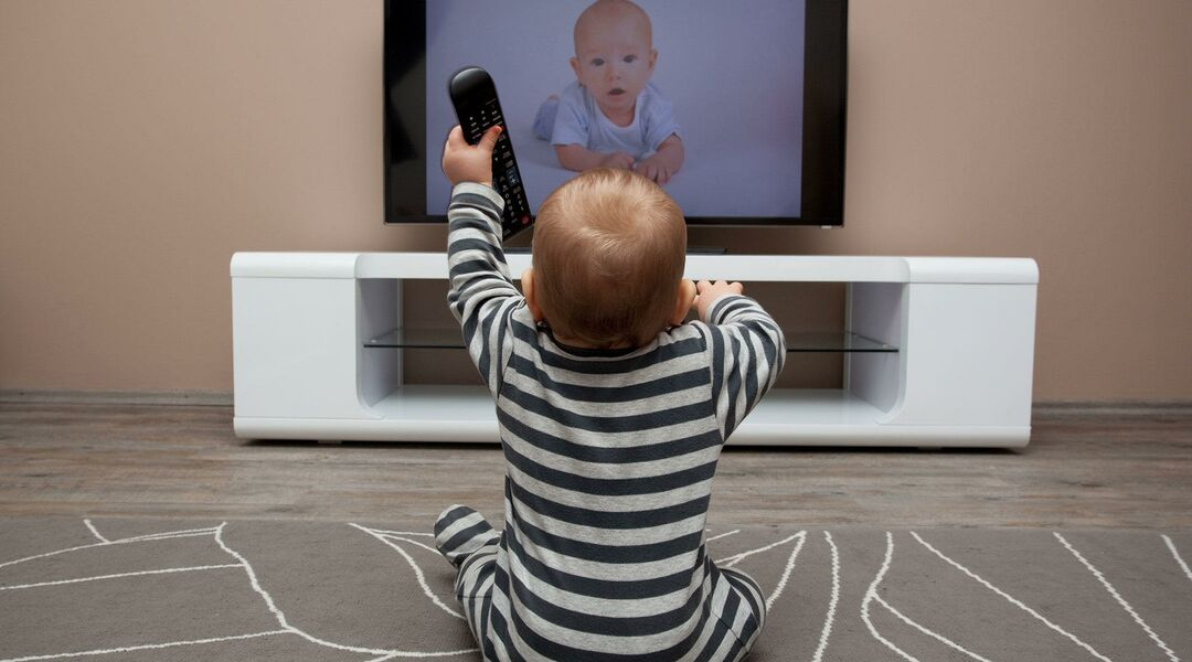 baby with remote in hand watching television