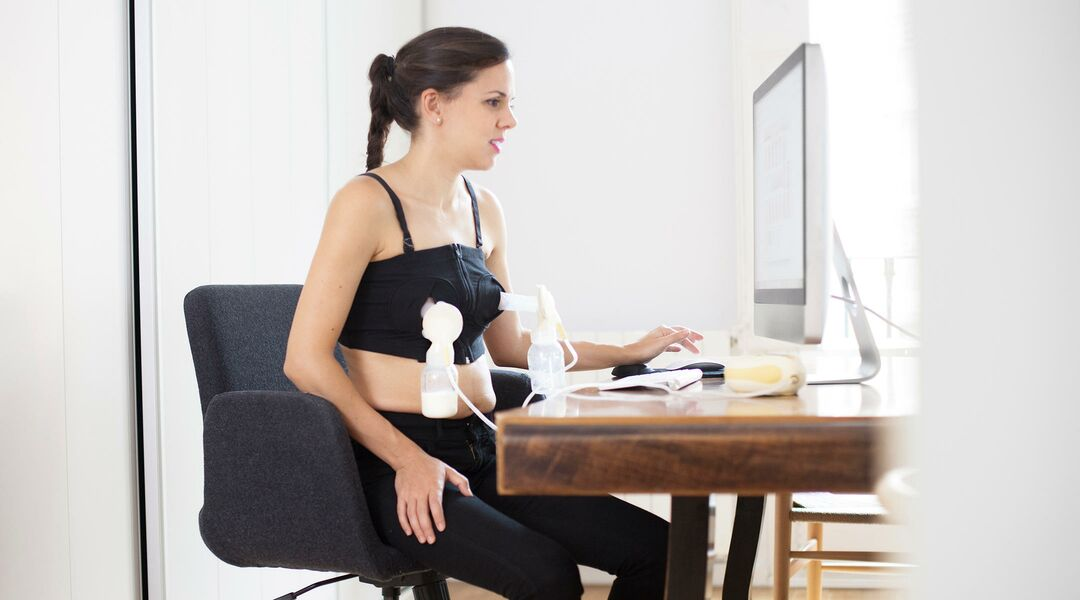Woman using a hands-free breast pump at her computer