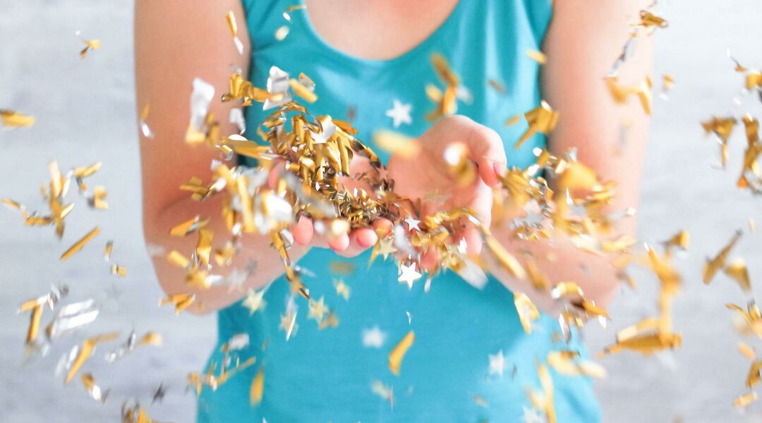 woman throwing gold confetti