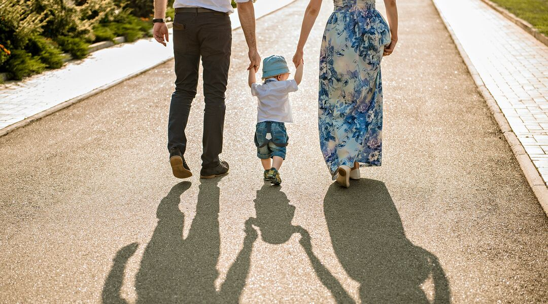 Two parents walk with their child, each holding one of the child's hands