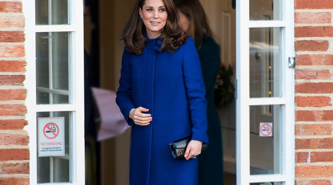 Kate Middleton standing in blue dress.