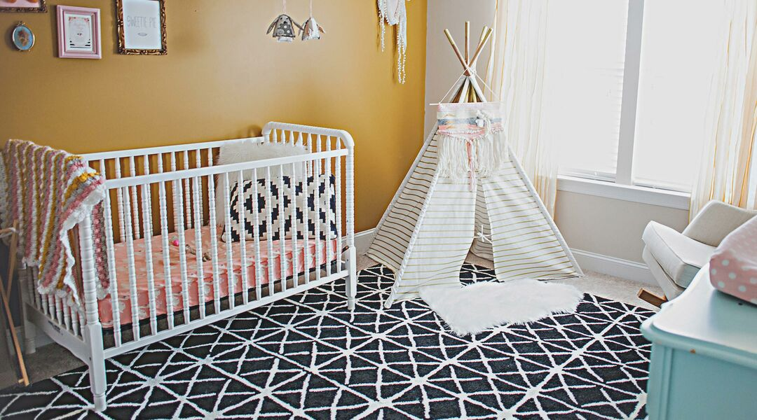 Baby nursery room with white crib and tee-pee.