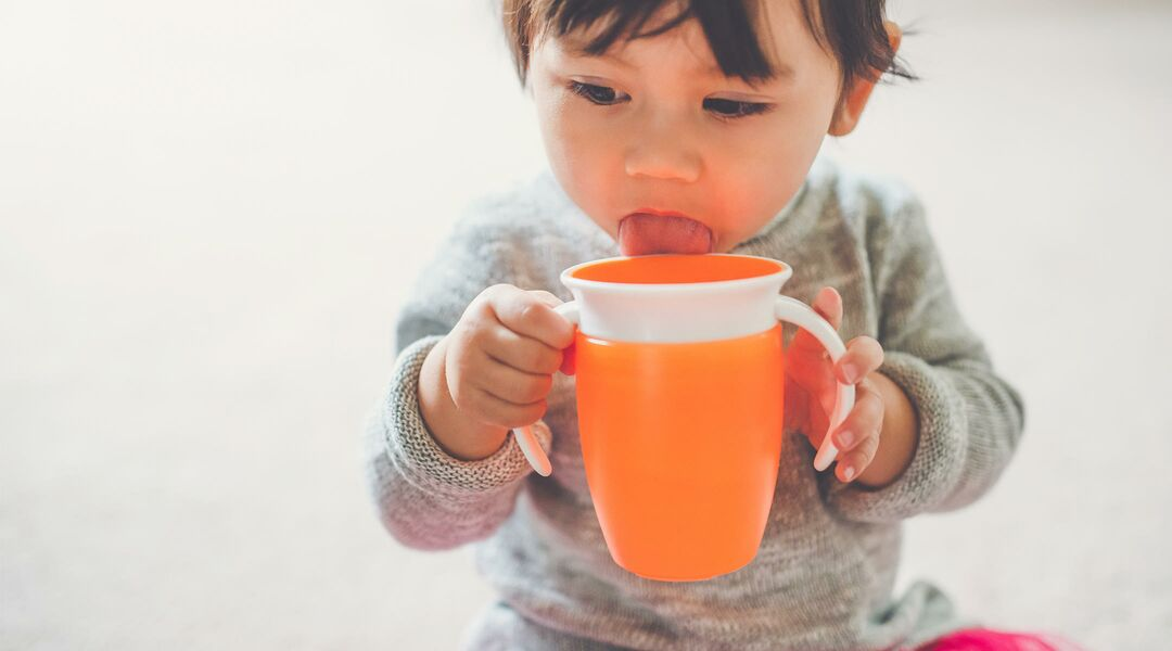 toddler drinking from orange sippy cup