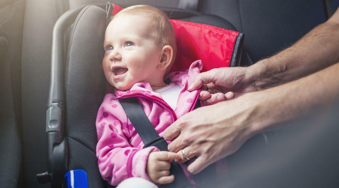 man buckling baby girl into a car seat