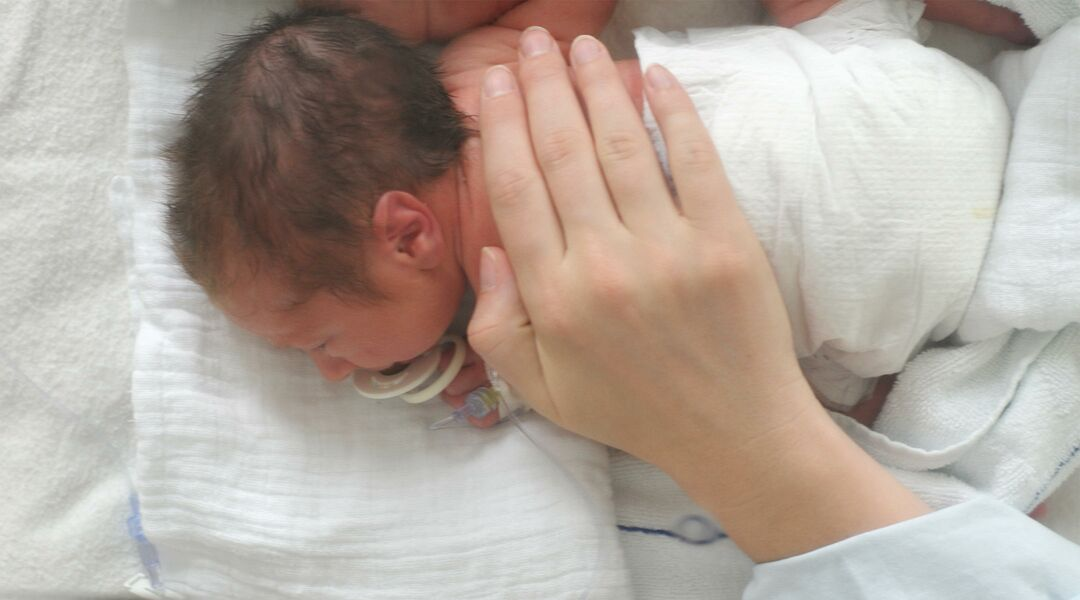 Parenting soothing sick newborn in hospital