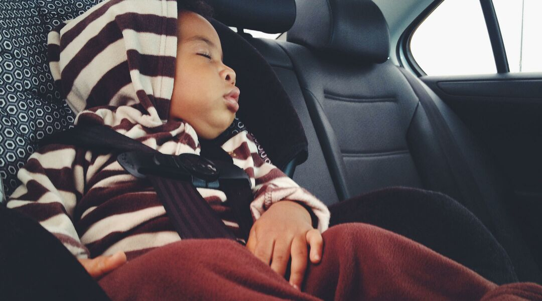 Child sleeping in car seat in a striped sweatshirt