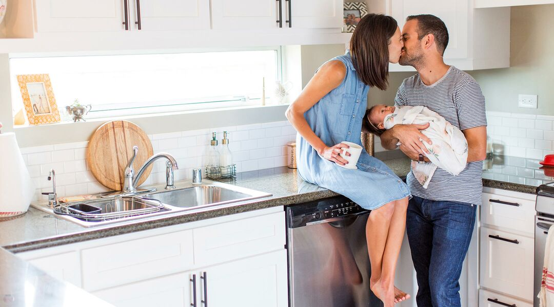 young couple with newborn in kitchen