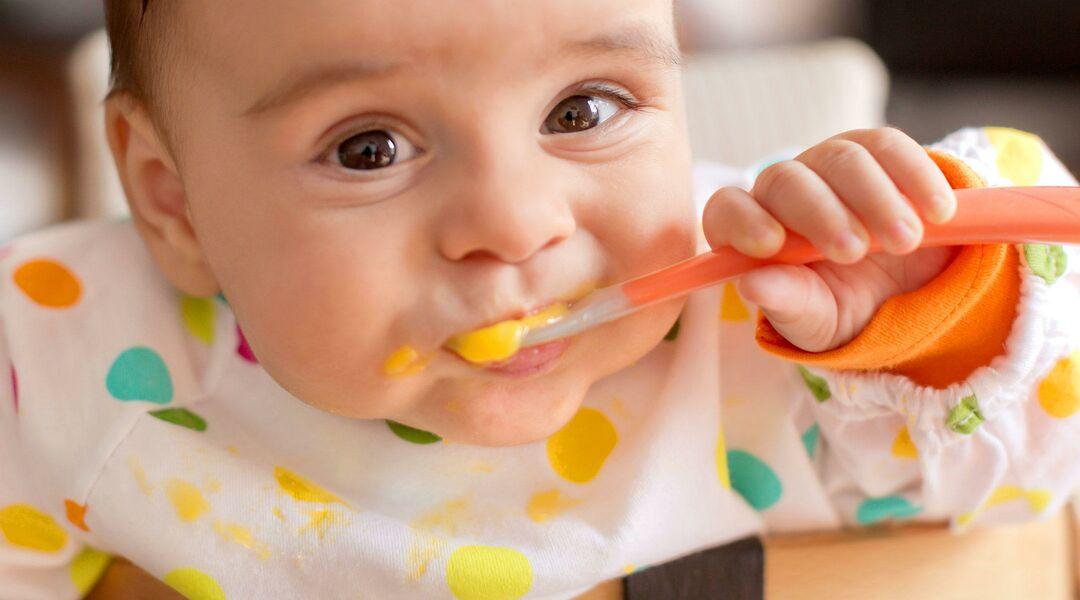 Smiling baby eating food.