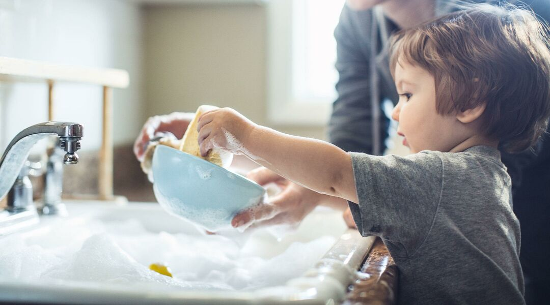 toddler helping mom clean dishes