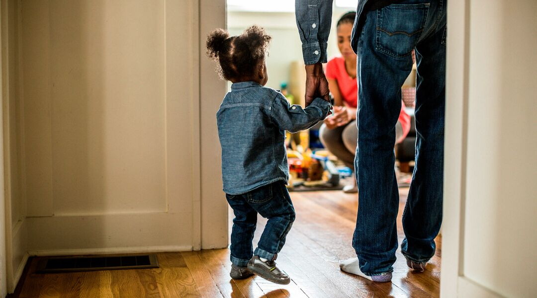 dad holding toddler daughter's hand and walking into room