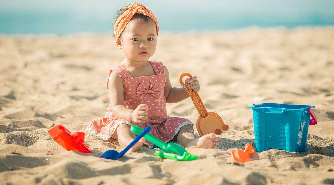 Baby girl at beach wearing infant swimwear