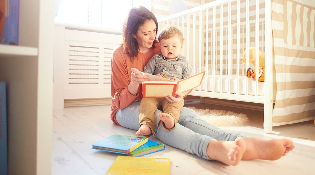 Mother reading to baby in the nursery