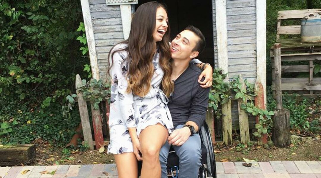 Woman laughing while sitting in the lap of man in wheelchair